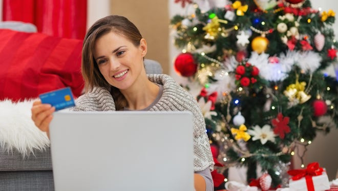 Happy young woman making online purchases near Christmas tree
