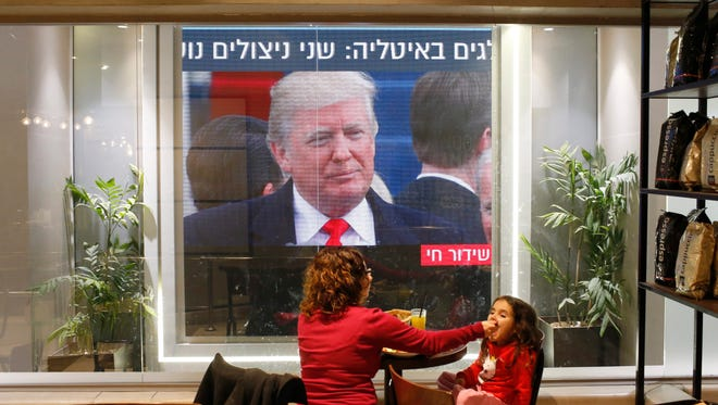 A woman and a child sit next to a screen showing the live broadcast of the inauguration of President Trump in a caffe in Tel Aviv, Israel, Jan. 20.