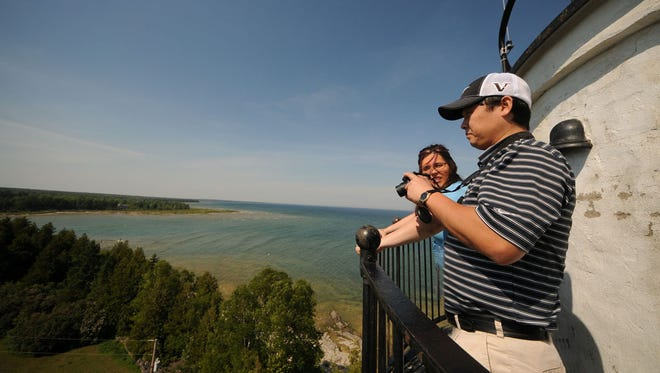Jacob and Tinya Dix of Dubuque, Iowa, take in the view from the top of the Cana Island Lighthouse off Baileys Harbor during a past year's annual Door County Lighthouse Festival.