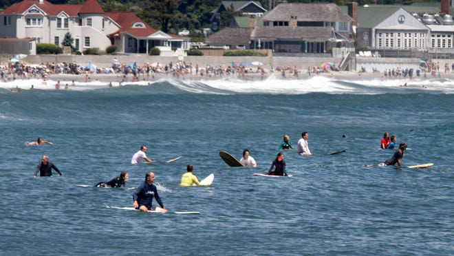 Surfers wait for the next big wave on a July afternoon in the water off Narragansett Town Beach.