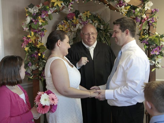 Steve Hoffman officiates at the 2011 wedding of Jamie and Melanie Farrell at his office.
