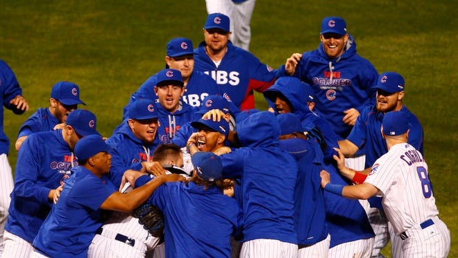 The Chicago Cubs celebrate after defeating the St. Louis Cardinals 6-4 in game four of the NLDS at Wrigley Field.