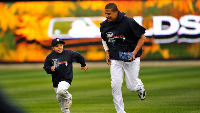 Victor Martinez and his son, Victor Jose, run in the Comerica Park outfield before a game in the ALDS in 2011.