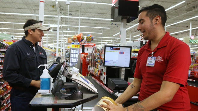 Chris Riojas (left) purchases Blue Bell ice cream from cashier Chris Zavala at the H-E-B Plus on Saratoga Boulevard on Monday, December 14, 2015.