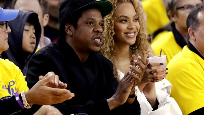 Jay-Z and Beyonce watch Game 1 of an NBA basketball second-round playoff series between the Golden State Warriors and the New Orleans Pelicans in Oakland, Calif., in 2018. They are among the musicians who have spoken out following the killing of George Floyd.