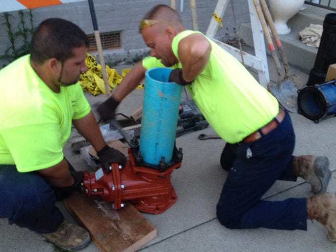 "Nate ""Rollie"" Hurtt, left, of Burlington, and Doug Wilmhoff, of Burlington, of Boone County Water District tighten fittings for the valve that will be replaced Thursday night at Jefferson and Washington streets in Burlington. The water district planned to shut down water to make repairs after several local restaurants were finished serving for the evening."