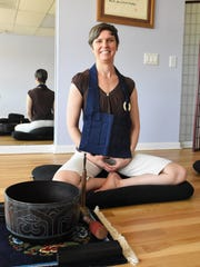Laurie Lyons, co-founder of Open Mind Zen Naples, poses inside the Naples studio on June 20, 2018. She wears a neck apron, symbolic of a Buddhist robe, after a meditation class.