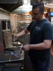 Ali Saleh flipping slicing lamb for gyros in the kitchen