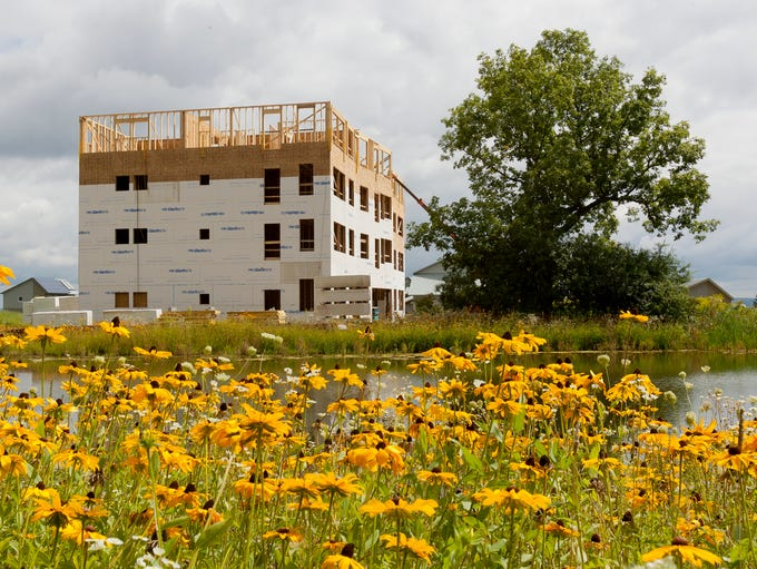 The four-story building that will contain the commonhouse and 15 apartments is the last piece to be completed of the third neighborhood at EcoVillage in the Town of Ithaca. The community worked to preserve the hickory tree in front of the building.