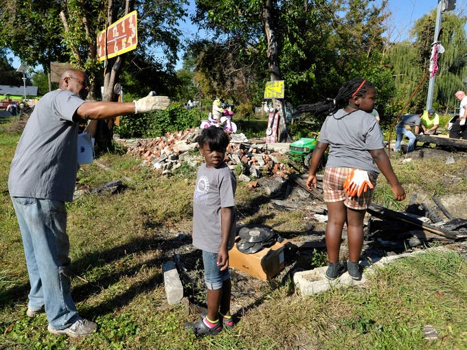 """Heidelberg Project creator Tyree Guyton, left, tells Delshawna Jones, center, 8, and her sister, Chardelle Jones, 9, both of Detroit, how they can help rebuild the """"House of Soul."""""""