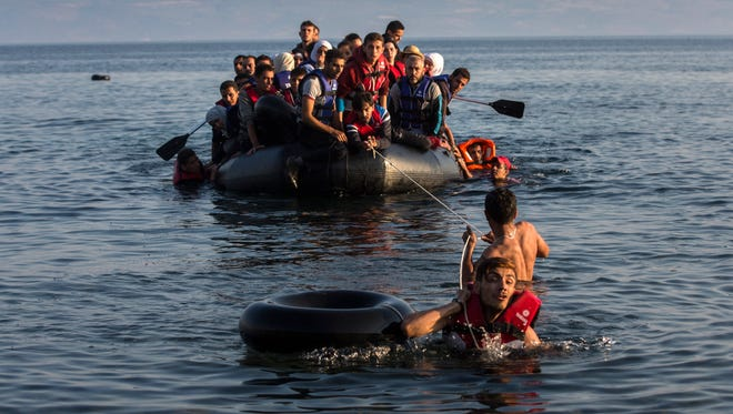 Two migrants pull an overcrowded dinghy with Syrian and Afghan refugees arriving from the Turkish coast to the Greek island of Lesbos on July 27.