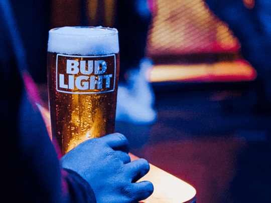 Hand holding glass of Bud Light beer