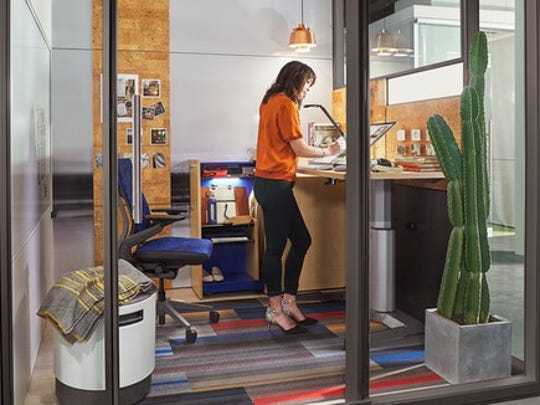 Employee at standing desk in a contemporary, glass cubicle office setting.