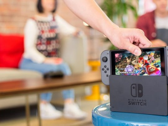 A person reaching for a Nintendo Switch.