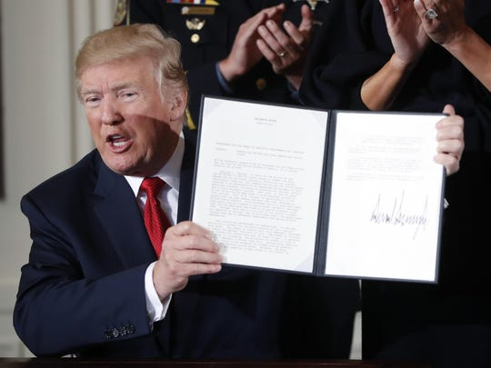 President Donald Trump displays a presidential memorandum he signed declaring the opioid crisis a public health emergency Thursday at the White House.