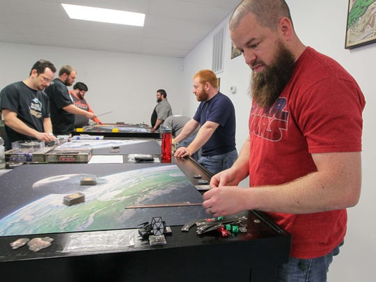Mike Meierholtz, right, manager of Empire Games in downtown Anderson, sets up to play in the Star Wars X-Wing tournament.