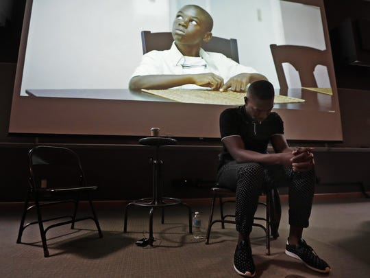 "Tarell McCraney waits to speak to students on Monday at Lawrence University in Appleton as a scene from ""Moonlight"" plays behind him. He received an Academy Award for Best Adapted Screenplay after co-writing the 2016 film, which is based on his own play, ""In Moonlight Black Boys Look Blue."""
