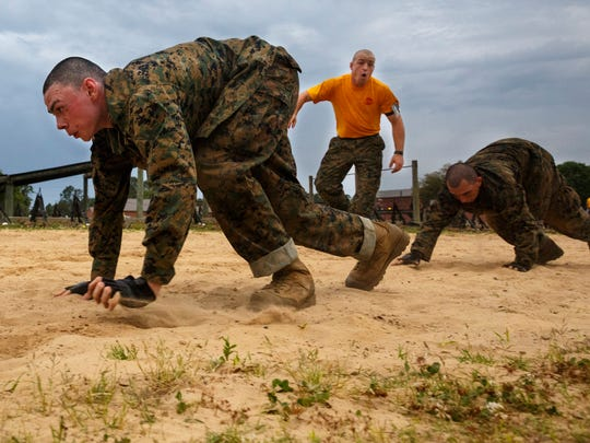 In this Thursday, April 28, 2016 photo, Marine recruits perform bear crawls as they go through morning PT at the Marine Corps Recruit Depot in Parris Island, S.C.