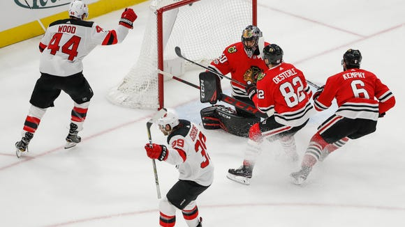 New Jersey Devils left wing Brian Gibbons (39) reacts after scoring against Chicago Blackhawks goalie Corey Crawford (50) during the second period of an NHL hockey game, Sunday, Nov. 12, 2017, in Chicago. (AP Photo/Kamil Krzaczynski)