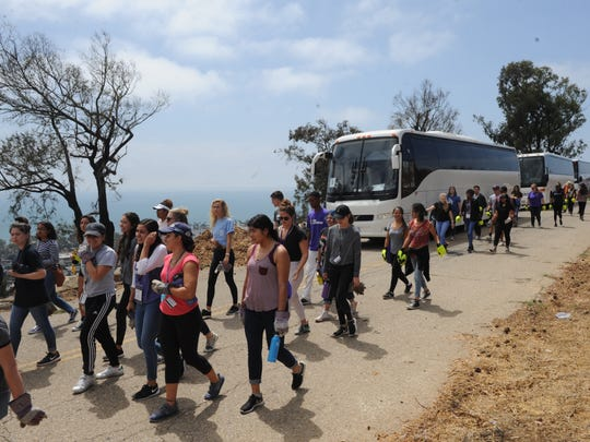 About 650 incoming California Lutheran University students exit buses to help clean up the hills above Ventura from the Thomas Fire. Bottles, debris and other trash was picked up and mulch was spread in Serra Cross Park, Ventura Botanical Gardens and other areas of Grant Park.