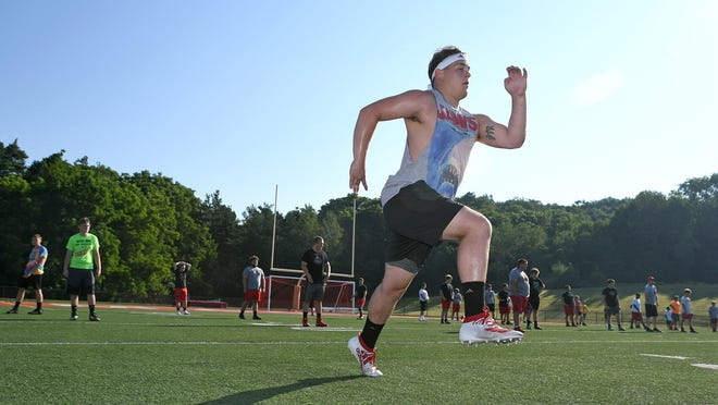 Football player Shamus Ford, foreground, completes a strength and agility exercise July 9 at General McLane High School in Washington Township. All sports teams in Pennsylvania are following safety protocols, including the wearing of face masks and social distancing when not competing, and daily temperature checks to slow the spread of COVID-19, the new coronavirus.