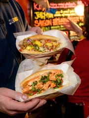 A customer shows late night sandwiches from WiLDWiCH food truck at 2015's Halloween Loop in Wilmington's Trolley Square.