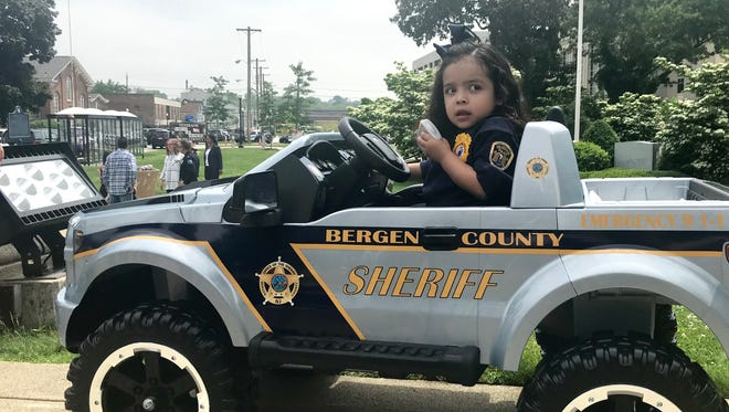 Isabel Vasquez, 4, radios Fairview Police Chief Martin Kahn for assistance during Bergen County's 7th annual Police Chief for a Day program.