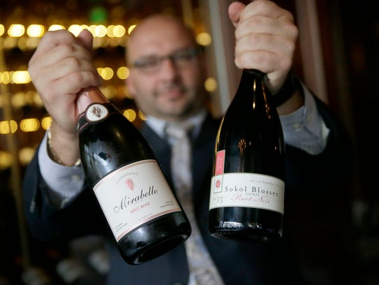 Jason Wedner holds two wines he suggests for Thanksgiving