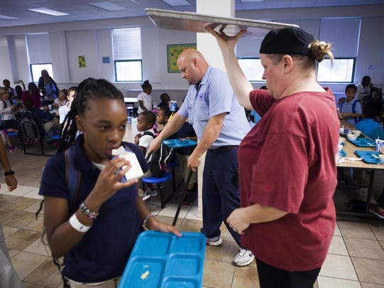 """Lester Greene, center, the head custodian for Bass Elementary in Lynchburg, cleans up as students eat lunch at the end of their intersession half-day on Sept. 3, 2015. """"For this neighborhood, and the kids in this area, I think they need extra help and the school gives them that,"""" said Greene, who grew up in the area, attended the school as child and has two kids that are currently enrolled at Bass."""