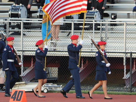 The Polytech color guard marches out onto the field for the season opener against Delcastle Thursday night.
