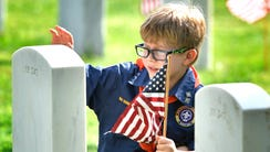 Jackson Cooper, 7, pats the headstone of a veteran