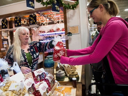 "Jacki Mack, owner if Dawg Gone Bees Apiary and Meadowy, helps customer Karla Gruendler and Frank Nazay with a gift box of honey-based items Saturday Nov. 26, 2016 during Small Business Saturday at The Markets of Hanover. ""It's better quality and you get to meet the people who make it,"" said Nazay of shopping local."