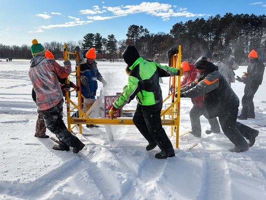 Volunteers use a chainsaw mounted on skis attached