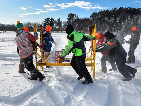Volunteers use a chainsaw mounted on skis attached to a cable to mark the circumference of a spinning ice carousel on Green Prairie Fish Lake on Jan. 6, 2018 near Camp Ripley.