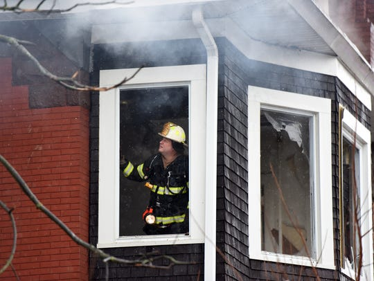 A Paterson firefighter looks at the structure inside
