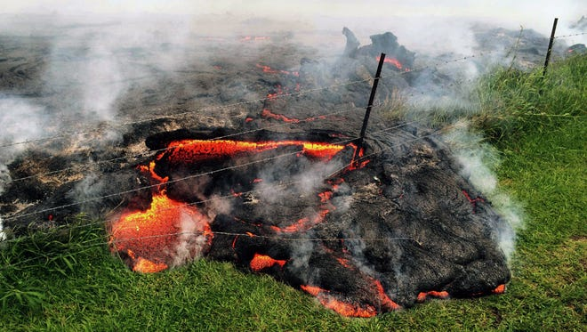 Lava flow advances Oct. 25 across the pasture between the Pahoa cemetery and Apaa Street, engulfing a barbed wire fence, near the town of Pahoa on the Big Island of Hawaii.