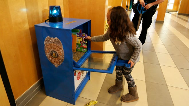 Sheboygan Police Officer Matthew Heimerl, background, stands as his daughter Briella, 5, opens the little free library that was created from a Sheboygan Press paper box, Wednesday, October 18, in Sheboygan. Heimerl noticed the proliferation of small libraries in the city while on duty. He felt it was a way to encourage reading for children if they happen to visit the station with their parents.