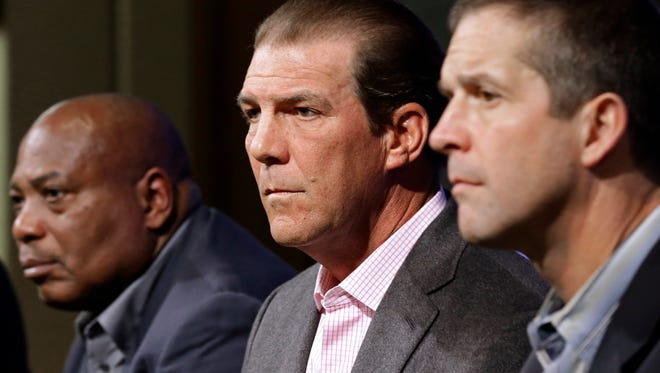 Baltimore Ravens owner Steve Bisciotti, center, listens to a reporter's question as he sits between general manager and executive vice president Ozzie Newsome, left, and head coach John Harbaugh at an NFL football news conference, Tuesday, Feb. 24, 2015, in Owings Mills, Md. The team held the news conference to review the 2014 season and discuss the upcoming season.
