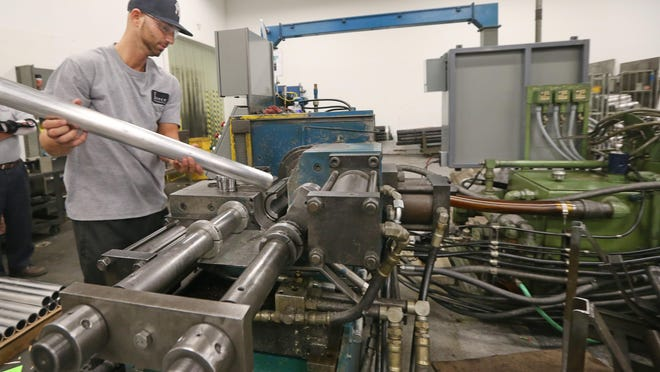 Jim Calaci loads an aluminum roller into a inertia friction welder at Pierce Industries. The company has benefited from a U.S. Small Business Administration loan.