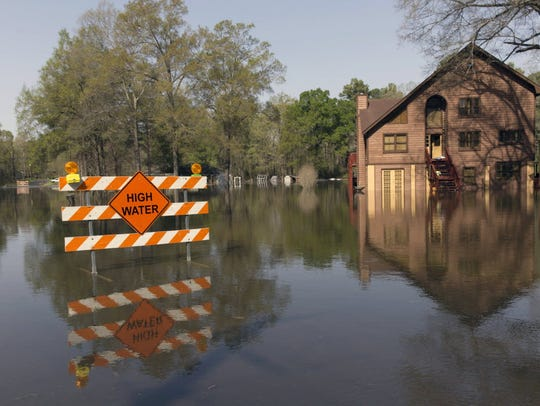 A sign marks high water in a flooded section of in