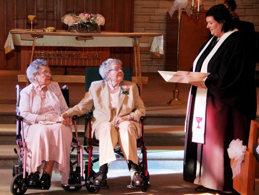 "In this Sept. 6, 2014 photo, Rev. Linda Hunsaker presides over the wedding of Vivian Boyack, left, and Alice ""Nonie"" Dubes, center, in Davenport, Iowa. More than seven decades after beginning their relationship, Boyack, 91, and Dubes, 90, got married."