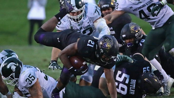 Michigan State's defense smothers Northwestern running back Justin Jackson on Saturday in Evanston, Illinois.