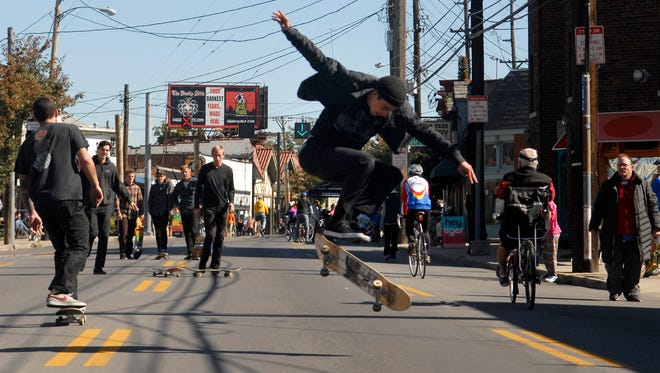 Ryan Tassi, 23, does a kick flip in the street outside HOME Skateshop during the 4th annual CycLOUvia on Bardstown Rd. Sunday afternoon.    October 18, 2015
