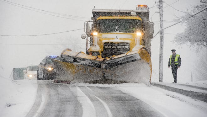 Police stop traffic so a snow plow can clear and salt a hill on North George Street in Manchester Township earlier this winter. More snow is in the forecast for the first day of spring.