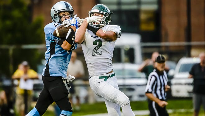 Lansing Catholic's Konnor Maloney, left, rips the ball away from Sy Barnett of Williamston for an interception last week. Maloney has three interceptions this fall for the Division 5 No. 3-ranked Cougars.