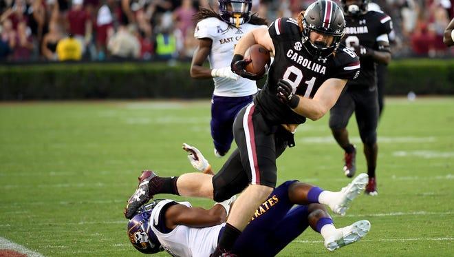 The University of South Carolina's Hayden Hurst (81) is tripped up by East Carolina University's Travon Simmons (3) at Williams-Brice Stadium on Saturday.