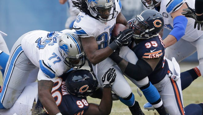 Detroit Lions running back Joique Bell (35) is tackled by Chicago Bears defensive tackles Brandon Dunn (98) and Ego Ferguson (95) during a game in 2014.