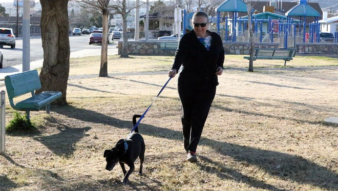 "Katie Hudak of El Paso takes her dog Negrilla for a stroll around Mary Webb Park at 3401 E. Missouri Ave. Thursday afternoon. They visit the park ""Almost every day,"" Hudak said."