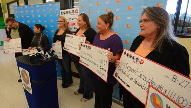 Members of a group of nine lottery winners, co-workers at APAC Customer Services in Green Bay, show off their checks at Festival Foods in Bellevue in October 2014. The group split $1 million in Powerball winnings.