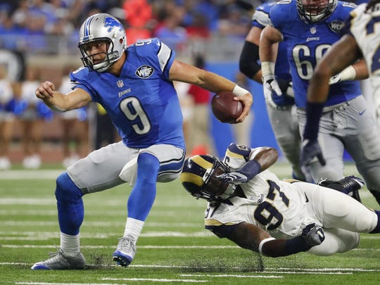 Matthew Stafford eludes Rams defensive end Eugene Sims.
